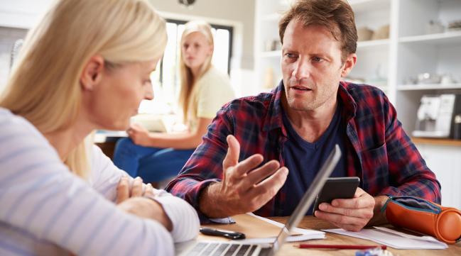 Mann und Frau am Arbeitsplatz mit Laptop und Smartphone. (verweist auf: Ich möchte einen IT-Sicherheitsvorfall melden.)