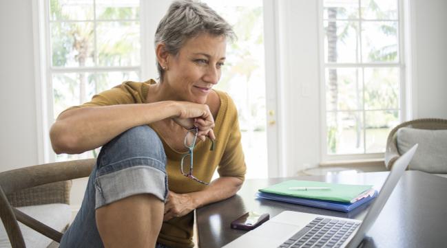 Frau mit Laptop am Schreibtisch (verweist auf: Ich suche aktuelle Informationen über IT-Sicherheitsbedrohungen.)